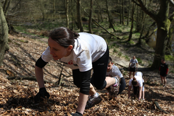 Spartans scrambling up hill using bear crawl